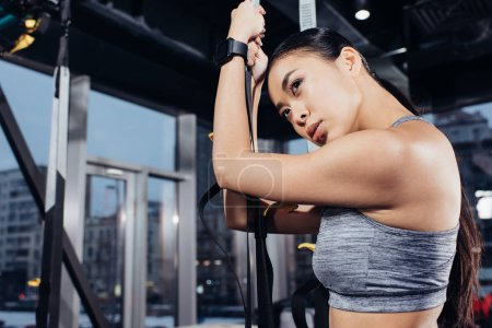 close up view of asian sportswoman holding resistance bands at gym