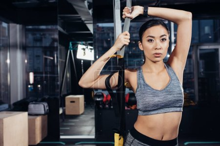 Photo for Slim asian sportswoman holding resistance bands at gym - Royalty Free Image