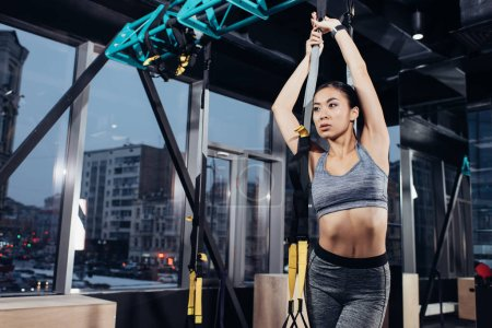 slim asian girl in sportswear training with resistance bands at modern gym