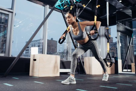 attractive asian girl in sportswear training with resistance bands in sports center