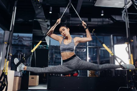 attractive asian sportswoman doing split with resistance bands at gym