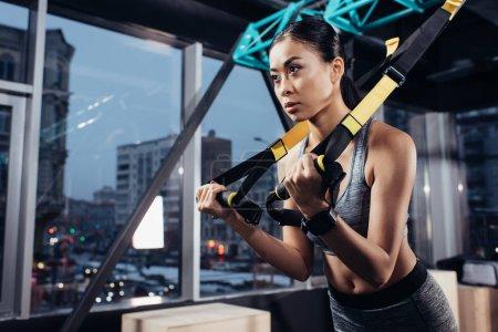 Photo pour Sportive asiatique athlétique, formation avec les bandes de résistance dans un centre de fitness - image libre de droit
