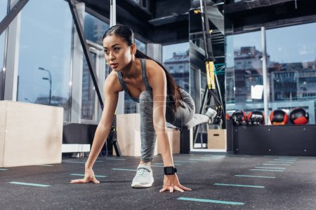slim asian girl stretching leg with resistance bands at gym