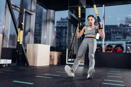 Photo for Athletic asian girl exercising  with resistance bands in sports center - Royalty Free Image