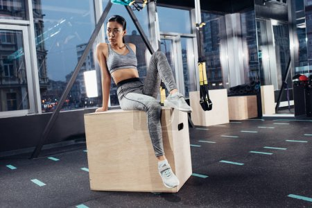 attractive asian sportswoman sitting on big wooden cube in sports center