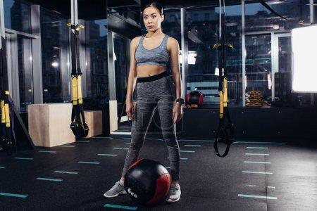 slim asian girl standing near medicine ball at gym