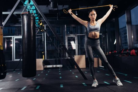 athletic girl holding skipping rope at gym