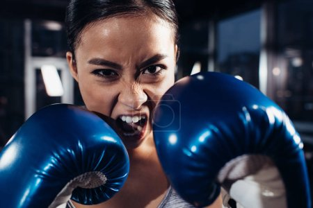 close up view of shouting girl in boxing gloves