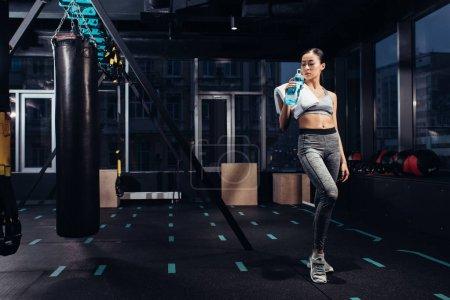 Photo pour Athlétique asiatique fille tenant bouteille de sport avec de l'eau à la gym - image libre de droit