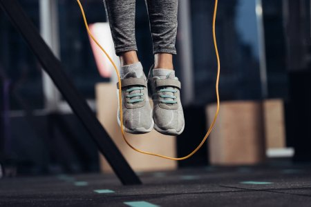 cropped view of female legs jumping with skipping rope at gym