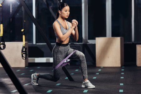 attractive asian girl training with rubber resistance bands in modern gym