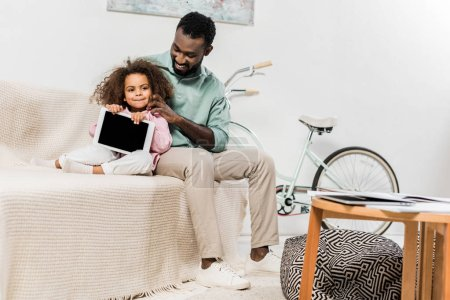 african american father and daughter using digital tablet and sitting on couch