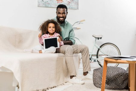 african american father and daughter sitting on couch and looking at camera