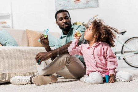 Photo pour Afro-américaine famille assis sur le plancher et soufflant des bulles de savon - image libre de droit