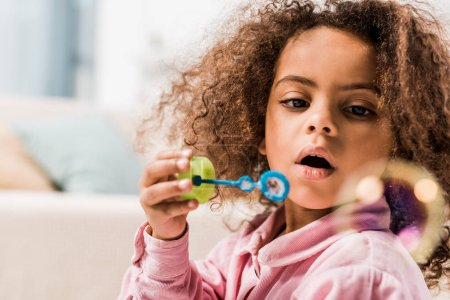 curly african american kid blowing soap bubbles at home