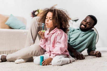 african american father and daughter comfortably sitting on floor and making soap bubbles