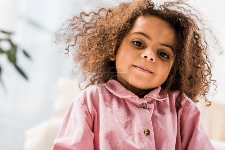 beautiful curly african american child looking at camera and smiling
