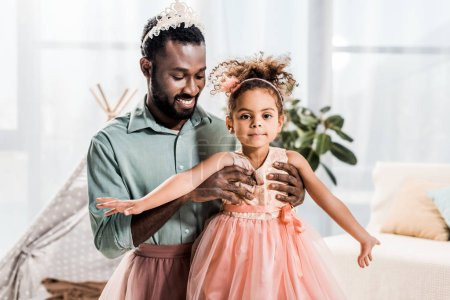happy smiling african american father lifting up beautiful daughter in pink dress