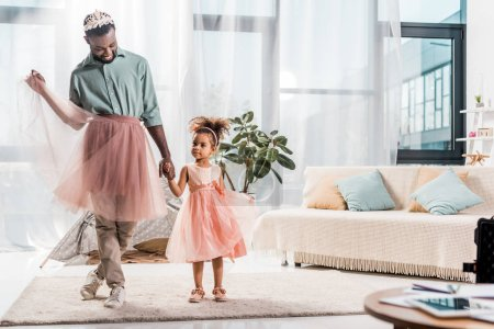 happy african american father in cute pink tutu and adorable daughter in beautiful dress