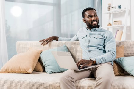african american freelancer sitting on couch in living room and looking away