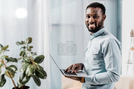 african american freelancer smiling and holding laptop