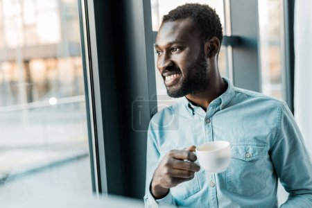 Photo for Handsome african american man holding cup of coffee while looking out of window - Royalty Free Image