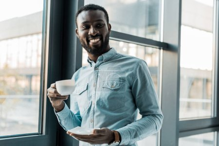 african american man holding cup of coffee and looking at camera