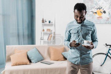 Photo pour Souriant afro-américain tapant sur smartphone et tenant la tasse de café - image libre de droit
