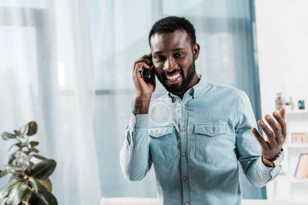 african american man talking on smartphone in living room
