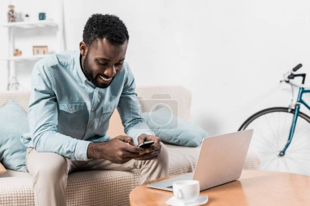 Photo for African american freelancer sitting on couch and typing on smartphone - Royalty Free Image