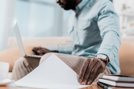 cropped view of african american freelancer touching papers while working on laptop