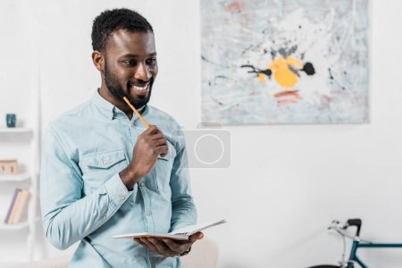 smiling african american man holding pencil and notepad