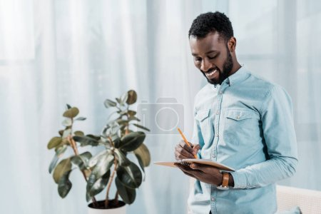 smiling african american man writing in notepad