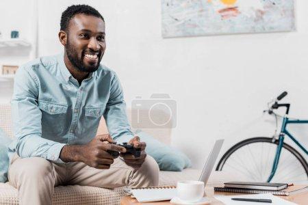 Foto de Hombre del afroamericano jugando video juego con joystick en casa - Imagen libre de derechos