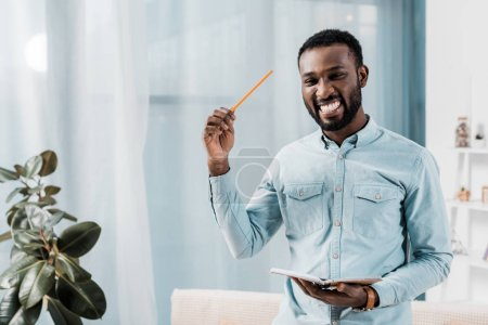smiling african american freelancer holding notepad and pencil while looking at camera