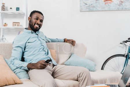 happy african american man sitting on couch with remote controller