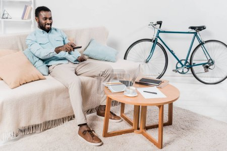 african american man sitting with remote controller on couch in living room
