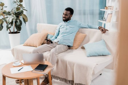 african american man watching TV and sitting on sofa in living room