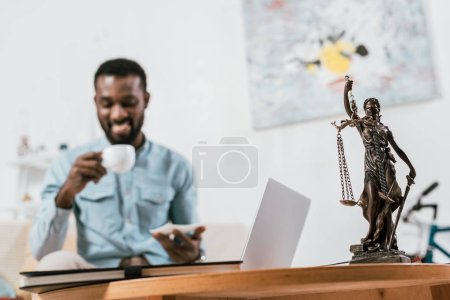 selective focus of scales of justice on table with blurred african american man at background
