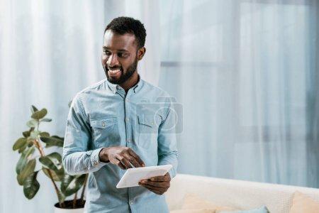 Photo pour Homme afro-américain utilisant une tablette numérique et regardant loin dans le salon - image libre de droit
