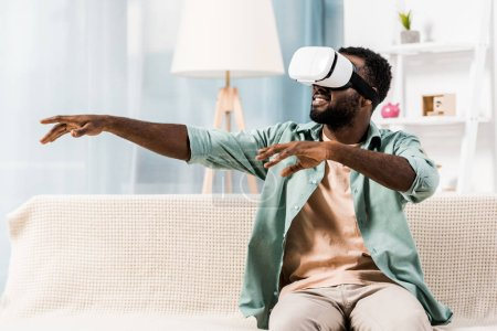 Photo for African american man using virtual reality headset in living room - Royalty Free Image