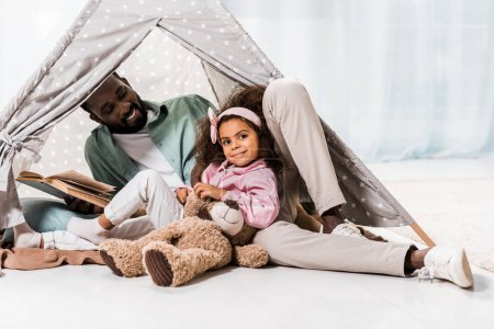 african american father reading book with child and smiling in wigwam