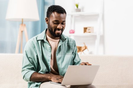 Photo pour Homme afro-américain travaillant sur ordinateur portable dans le salon - image libre de droit