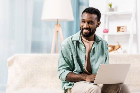 Afrikanisch-amerikanischer Mann benutzt Laptop und schaut im Wohnzimmer weg