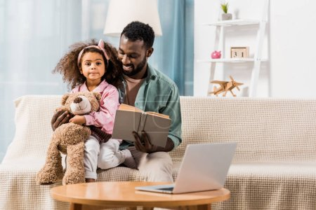 Photo for African american father reading book with daughter in living room - Royalty Free Image