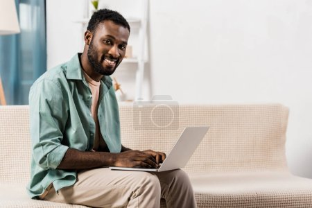 Photo for African american man using laptop on knees and looking at camera in living room - Royalty Free Image