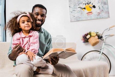 Foto de Americano africano padre con hija sentado en las rodillas en la sala de lectura - Imagen libre de derechos