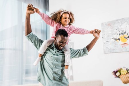 Foto de Hombre del afroamericano jugando con hija en sala de estar - Imagen libre de derechos