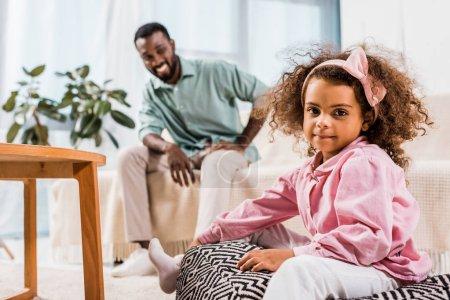 Photo pour Mise au point sélective de fille afro-américaine et père dans le salon - image libre de droit