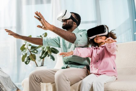 Photo for African american father and daughter using virtual reality glasses and smiling in living room - Royalty Free Image
